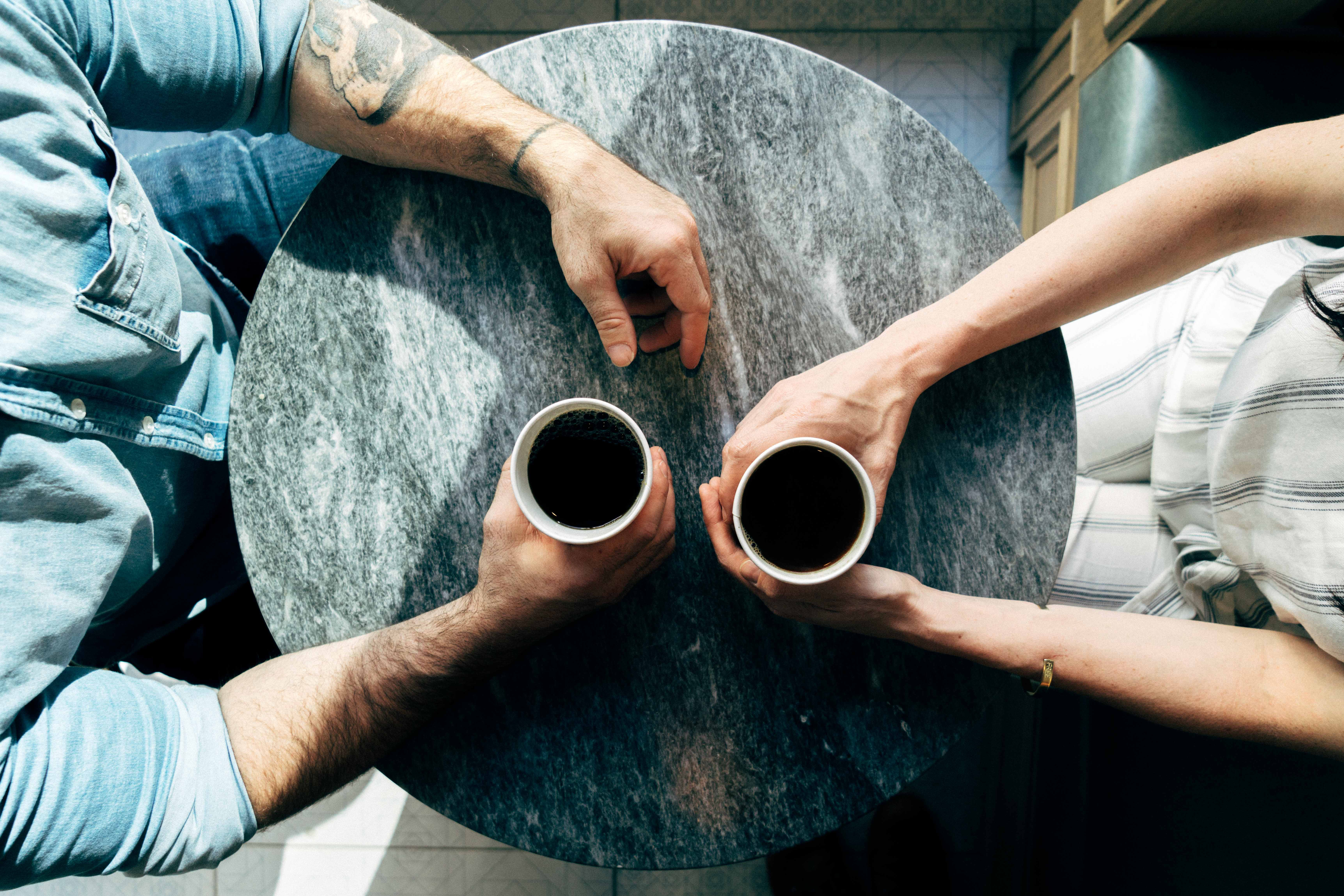Image of two people at a table with coffee