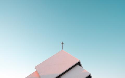 Image of a cross on the roof of a modern church