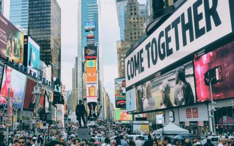 "Image of a big crowd in a city street; prominent advertisement including the words ""Come Together"""
