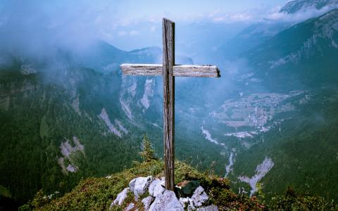 Image of a wooden cross on the top of a mountain.