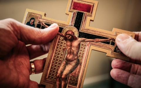 Image of a person holding a small crucifix in their hands