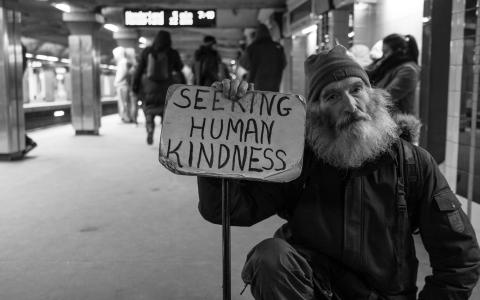 Image of a homeless man with placard saying seeking human kindness