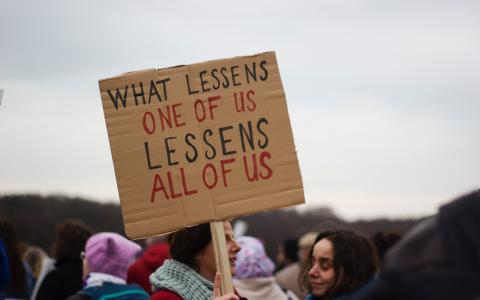 Placard saying What lessens one of us, lessens all of us