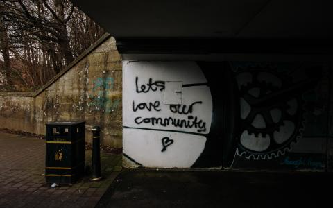 Graffiti on wall saying let's love our community