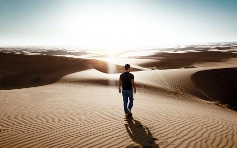 Image of a man walking in a desert
