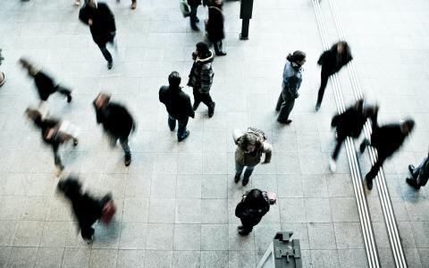 Image of people walking across concrete floor