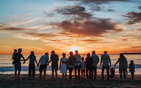 Family group looking at a sunset on a beach